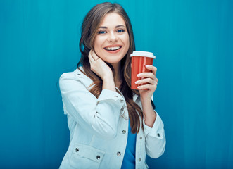 Smiling beautiful girl holding red coffee glass.