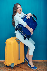 Smiling woman traveler sitting on yellow suitcase and holding blue bag.