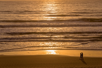 Wall Mural - Silhouettes of a couple enjoying the sunset on the atlantic ocean, Lacanau France