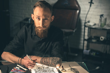 Wistful male with tattoo painting image