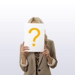 Frau hält Blatt mit Blatt mit Fragezeichen vor ihrem Gesicht