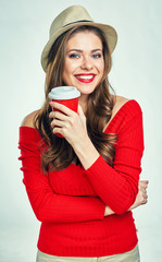 Beautiful smiling woman wearing red sweater holding red coffee cup.