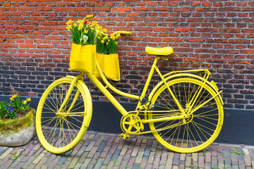 Foto auf Leinwand Fahrrad Vintage yellow bicycle with basket of daffodil flowers on old rustic brick wall background