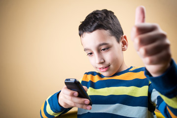 Boy with mobile phone showing you thumbs up.
