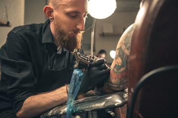Serene male doing tattoo in salon