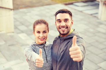 smiling couple showing thumbs up on city street