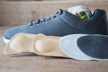 Running shoes with orthopedic insoles. Gray shoes. Wooden board.