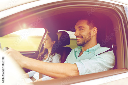 happy man and woman driving in car