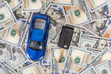 blue toy car with car key on dollar.