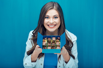 Smiling girl holding box with chocolate candies.