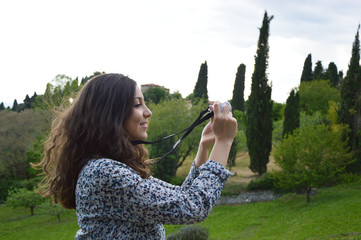 Young woman taking photos with a mirrorless in the nature