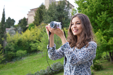 Smiling girl taking photos with a mirrorless camera in the nature
