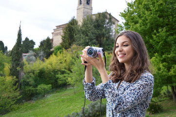 Smiling girl taking photos with a mirrorless in the nature
