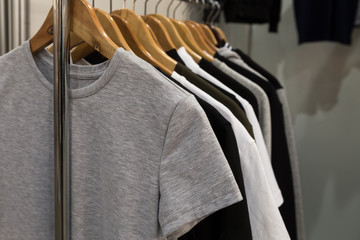 T-shirts black, gray and white monophonic hanging on holders