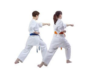 Friends sportswomen are training kick against white background