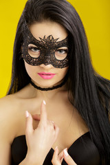 portrait of beautiful sensual woman in black lace mask on yellow background. sexy girl in venetian mask
