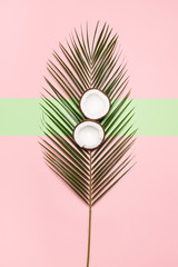 On a palm leaf, two halves of coconut on a pastel pink and green background. Minimal concept. Minimalism style
