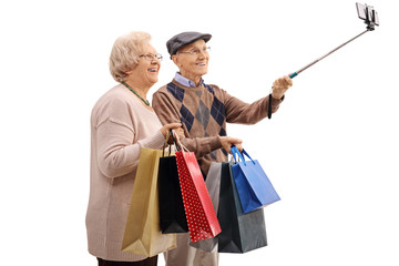 Cheerful senior couple with shopping bags taking a selfie