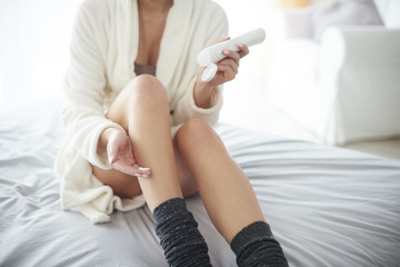 Young woman moisturizing her legs