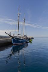 Ein altes Segelschiff mit zwei Masten am Kai mit Reflex im Wasser.
