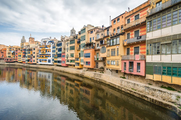 Cloudy view of riverside and bridge over river Onyar, Girona, Catalonia, Spain.