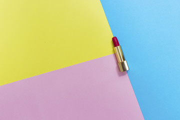Top view of makeup set: red lipstick on pastel background.