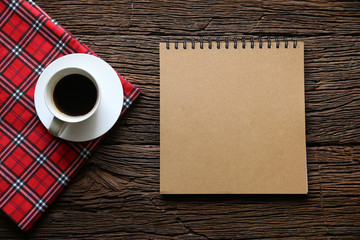 Hot coffee and note book paper texture mockup on wood table backdrop.Flat lay.Copy space