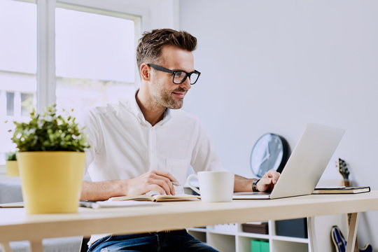Happy man working on laptop from home office