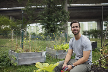 Portrait of smiling mid adult man sitting on edge of wooden crate at urban garden