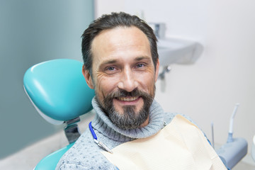 Smiling man in dental chair. Person at the dentist. Trust your smile to professionals.