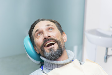 Mature person in dental chair. Man with opened mouth.