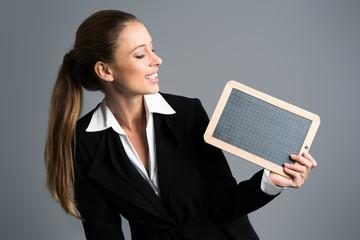 junge Geschäftsfrau mit leerer Schiefertafel