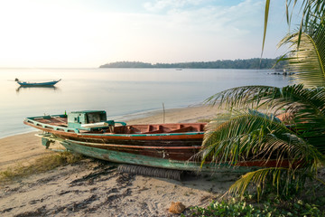 Old broken longtail boat on the Thai beach during the sunset