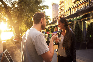 Couple having salad and water while standing on street during sunset