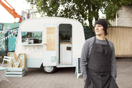 Thoughtful male owner looking away while standing outside food truck on street