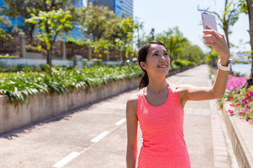 Sport Woman taking selfie by mobile phone in park