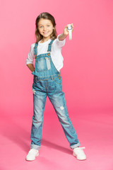 Adorable little girl in denim overalls holding smartwatch and smiling