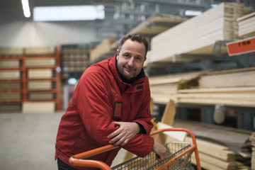 Portrait of confident salesman leaning on trolley in warehouse at hardware store