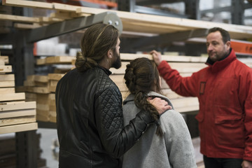 Salesman assisting couple with wooden planks in hardware store