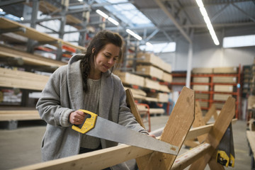 Female customer cutting wooden plank with handsaw in hardware store