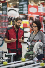 Salesman explaining power tools to mature woman in hardware store
