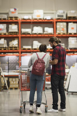 Full length of couple standing with shopping cart in hardware store