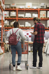 Full length rear view of couple discussing while walking in hardware store