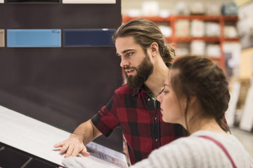 Couple examining tile while shopping at hardware store