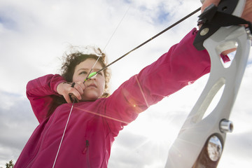 Low angle view of determined girl practicing archery on sunny day