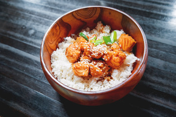Asian cuisine - rice in sauce with stir fried vegetables and salmon in wooden bowl. Close up.