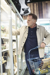 Mature man shopping at refrigerated section in supermarket
