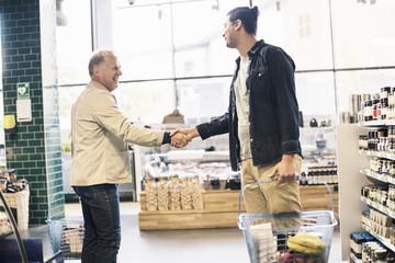 Happy men shaking hands in supermarket