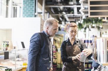 Saleswoman explaining product to man in organic supermarket
