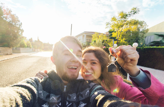 Happy young couple showing the keys to their new home and smiling